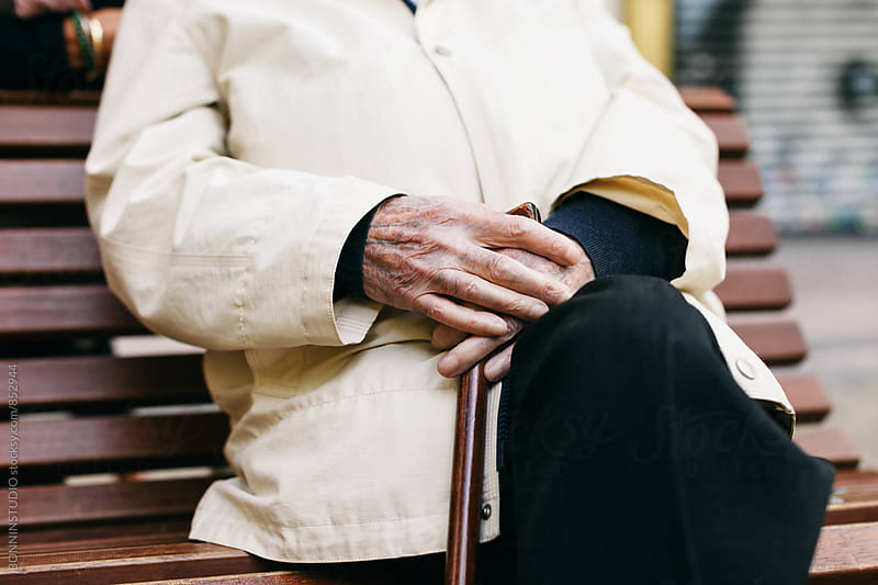 Closeup of an elderly man sitting on bench outside. by BONNINSTUDIO for Stocksy United