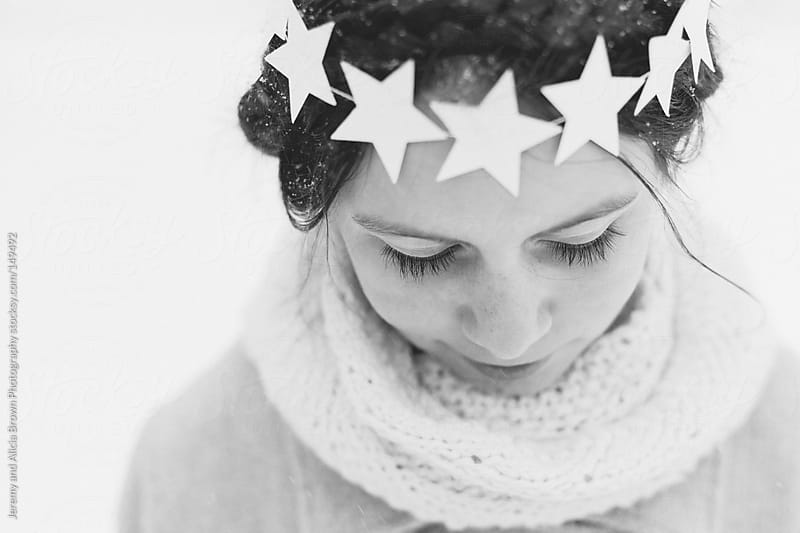 Little girl wearing a star wreath in the snow by Jeremy and Alicia Brown Photography for Stocksy United