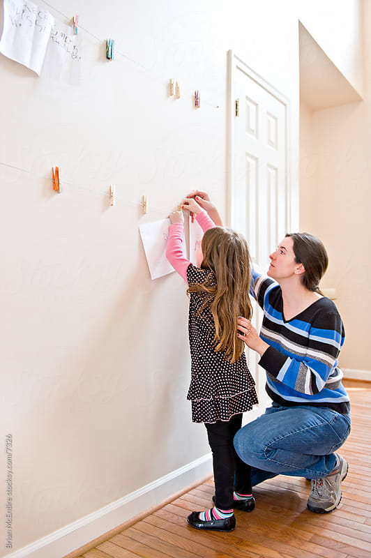 Young Girl and her Mom Hanging Child's Artwork on Wall in Home by Brian McEntire for Stocksy United