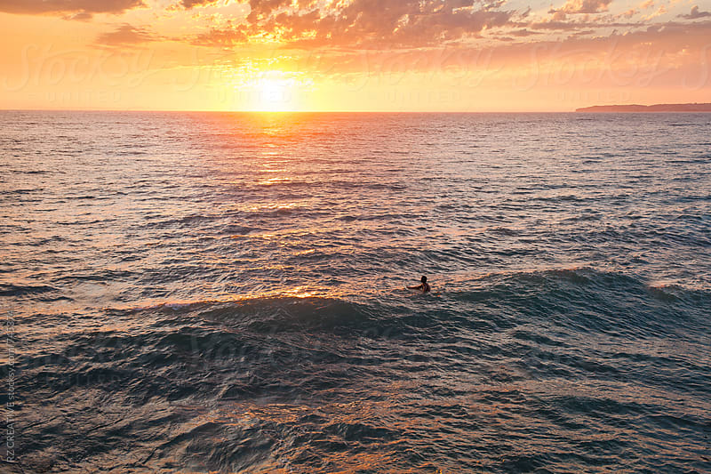 Surfer in the ocean watching a vibrant sunset over the sea. by RZ CREATIVE for Stocksy United