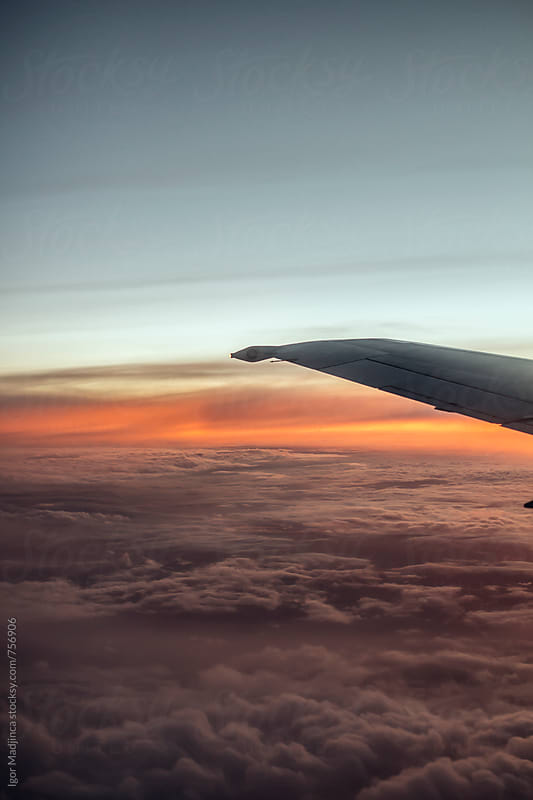 colorlull dramatic sunset, evening sky, aircraft flight by Igor Madjinca for Stocksy United