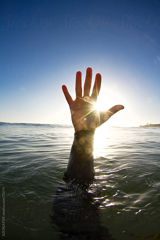 A hand reaching up out of the surface of the ocean in late afternoon light. by RZ CREATIVE for Stocksy United