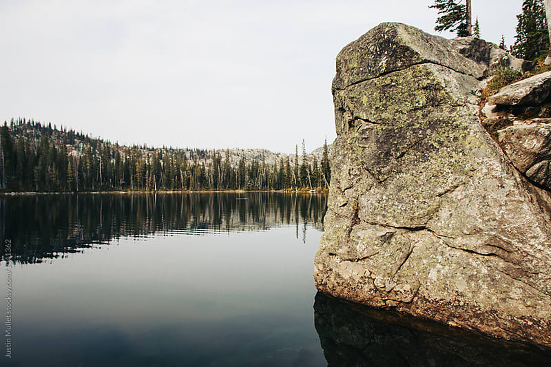 Large boulder on shore of alpine lake.  by Justin Mullet for Stocksy United