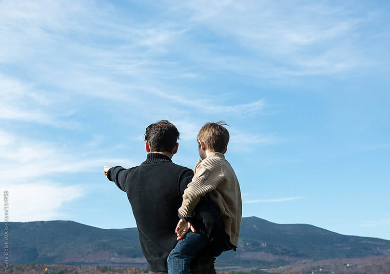 Father holds his son, pointing to mountains off in the distance by Cara Dolan for Stocksy United