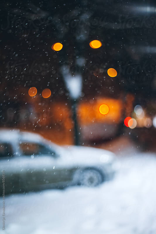 Snow covered sidewalk with parked car. Blurred image. by Dimitrije Tanaskovic for Stocksy United