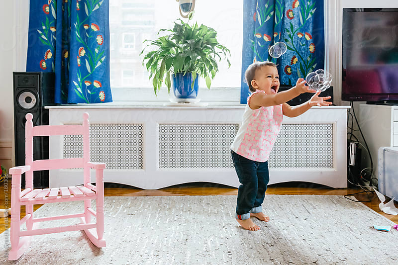 Toddler enchanted by bubbles by Jen Grantham for Stocksy United