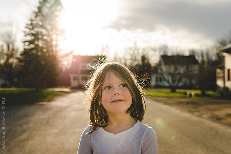 Girl standing in the street and looking at the sky by Lindsay Crandall for Stocksy United