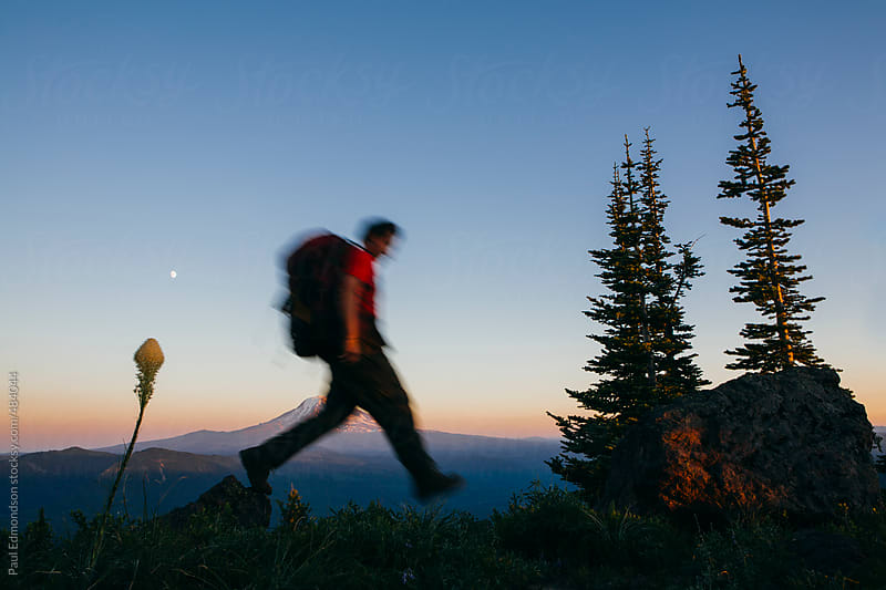 Man backpacking in mountains at dusk, Mt. Adams in distance by Paul Edmondson for Stocksy United