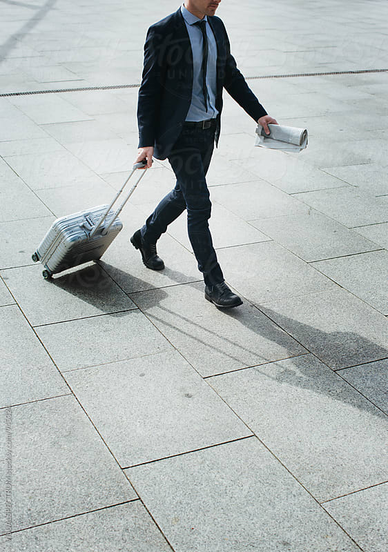 Smartly Dressed Caucasian Man Walking With Carry On Suitcase by Julien L. Balmer for Stocksy United