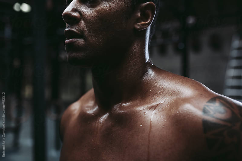 Young, fit black man recovering after training hard in fitness gym by Rob and Julia Campbell for Stocksy United