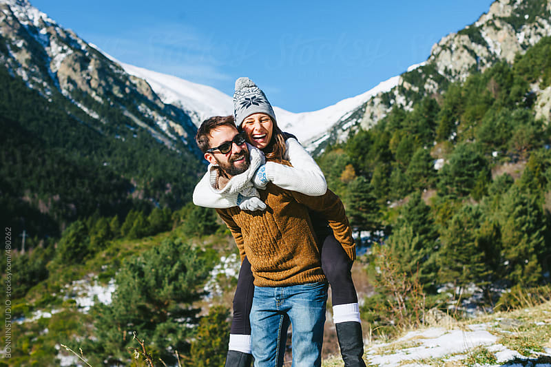 Young woman piggy backing on boyfriend in winter landscape.  by BONNINSTUDIO for Stocksy United