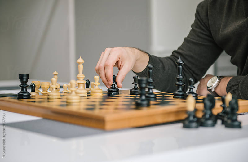 Male Hand Moving Chessman on the Chessboard  by Mosuno for Stocksy United