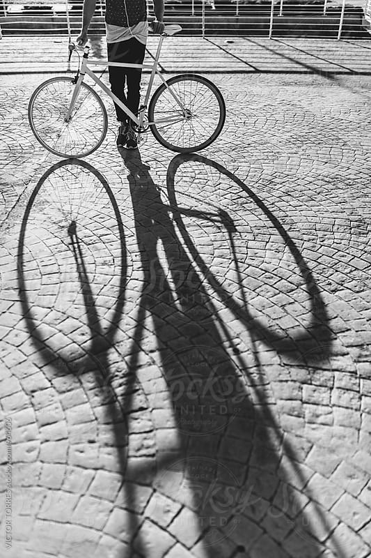 Shadow of a Bicycle on a Cobblestone Road by Victor Torres for Stocksy United