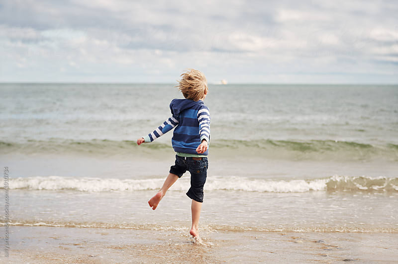 Child having fun playing on the beach by sally anscombe for Stocksy United