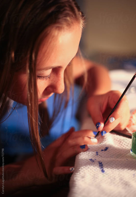 Young girl painting her nails by Carolyn Lagattuta for Stocksy United