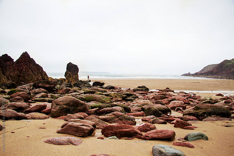 Red sandstone rocks on a beach by Helen Rushbrook for Stocksy United
