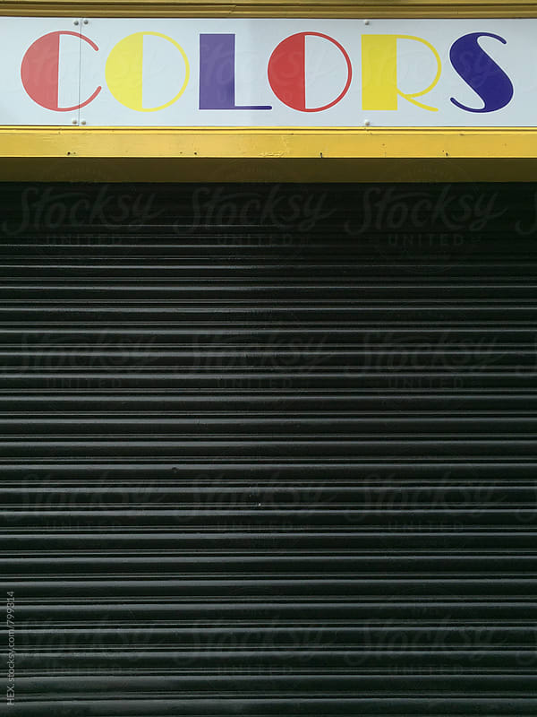 Colors Sign over a Grey Shutter Shop by HEX. for Stocksy United