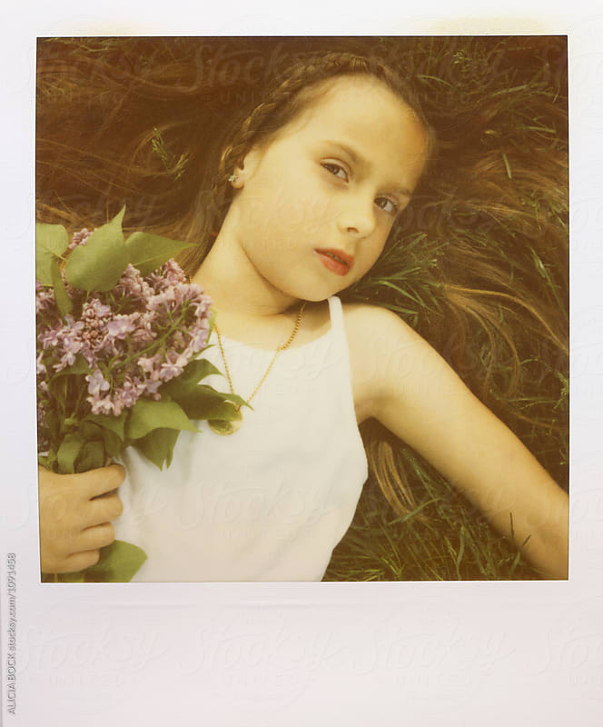 A Girl Holding Spring Lilac Flowers In The Grass Photographed With Expired Polaroid Film by ALICIA BOCK for Stocksy United