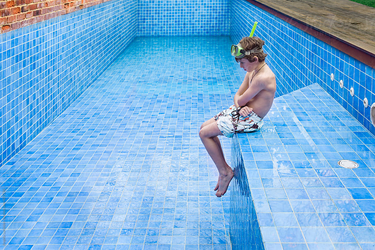 Stock Photo - Boy Sitting On The Edge Of A Blue Tiled Swimming Pool Waiting  For Water To Fill The Emptied Pool