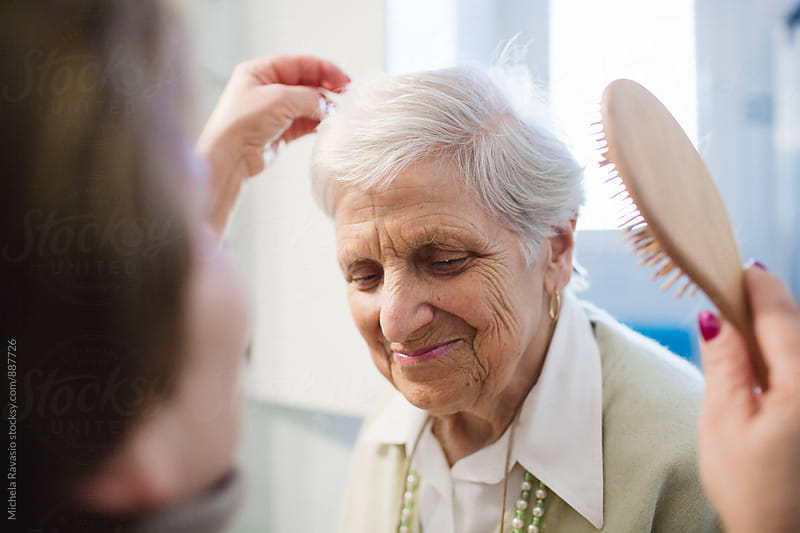 A caregiver brush the hair of an elderly lady by michela ravasio for Stocksy United