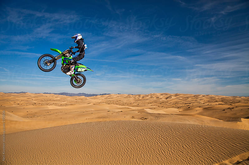 Motocross rider jumping sand dunes by Neil Kremer for Stocksy United
