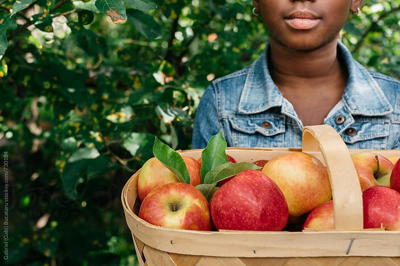 Basket of apples held by African American girl by Gabriel (Gabi) Bucataru for Stocksy United