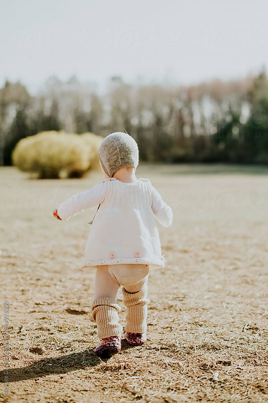 baby learning to walk by Michelle Gardella for Stocksy United
