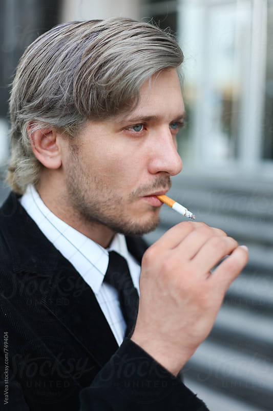 Portrait of a businessman smoking a cigarette  by VeaVea for Stocksy United