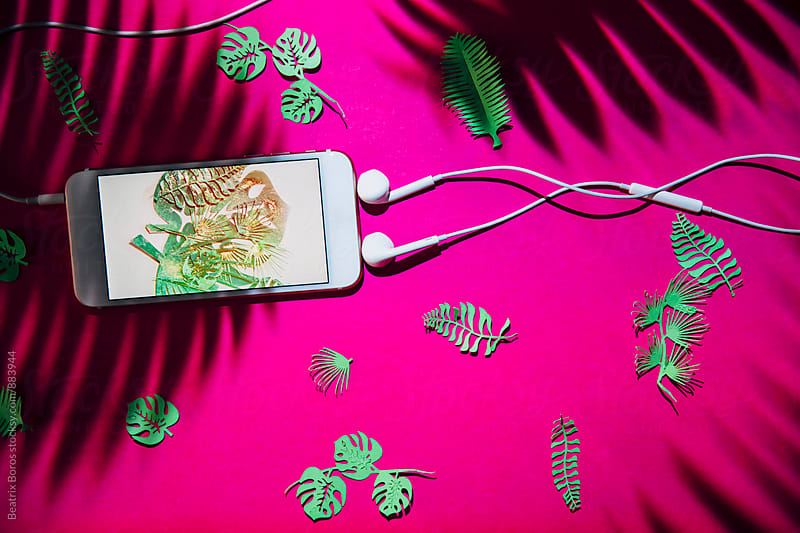 Smartphone with ear-buds shaping a music note symbol and green cut plants  by Beatrix Boros for Stocksy United