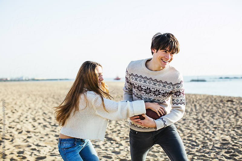 Teenage couple playing football on the beach. by BONNINSTUDIO for Stocksy United