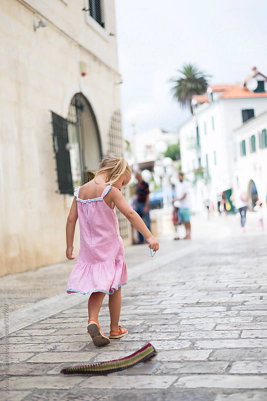 Beautiful little girl walking alone trough the city and pulling a snake toy in Mediterranean in summer by Jovana Milanko for Stocksy United