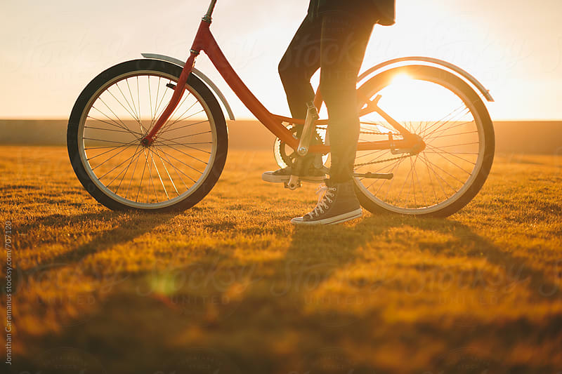 Bicycle silhouette on grass lawn  in golden light at sunrise or sunset by Jonathan Caramanus for Stocksy United