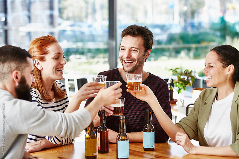 Business Friends Toasting Beer Glasses At Table by ALTO IMAGES for Stocksy United