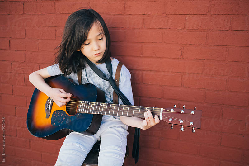 Young boy plays his guitar by kelli kim for Stocksy United
