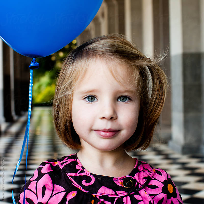 Girl and Blue Balloon by Thomas Hawk for Stocksy United