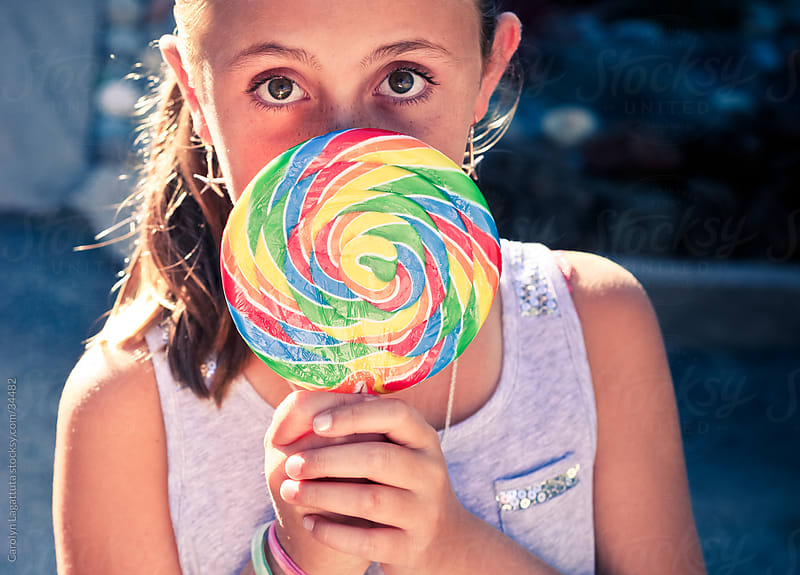 Young girl holding a huge lollipop in front of her face with big eyes peeking from behind it. by Carolyn Lagattuta for Stocksy United