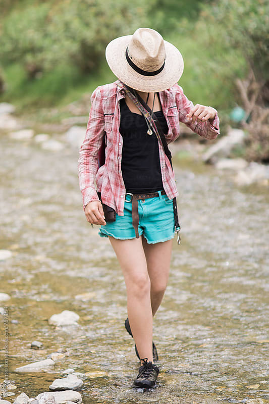 Fashionable female hiker walking in a creek by Per Swantesson for Stocksy United
