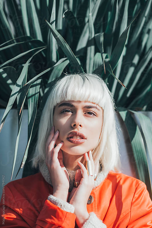 Young beautiful woman with white hair outdoors by Maja Topcagic for Stocksy United