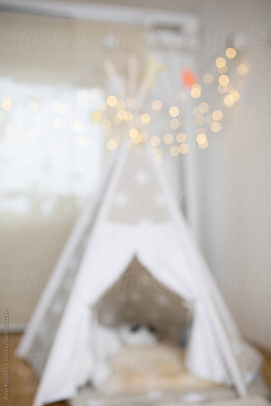 Blurred background of a kids indoor tent by Amir Kaljikovic for Stocksy United