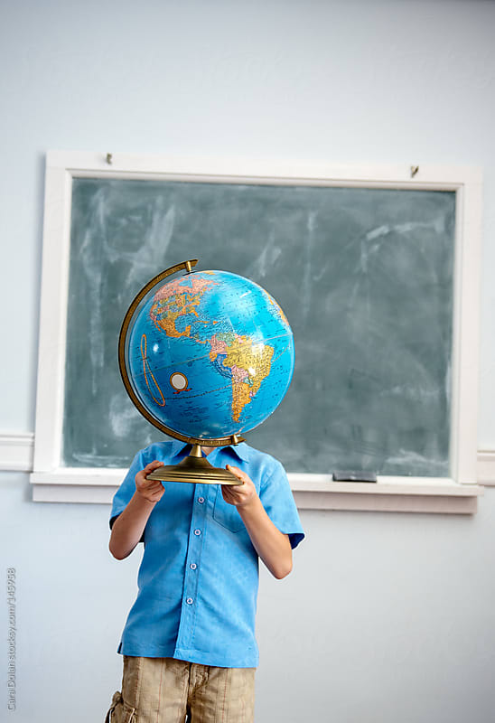 Student standing in classroom holds a globe up, covering his face by Cara Dolan for Stocksy United