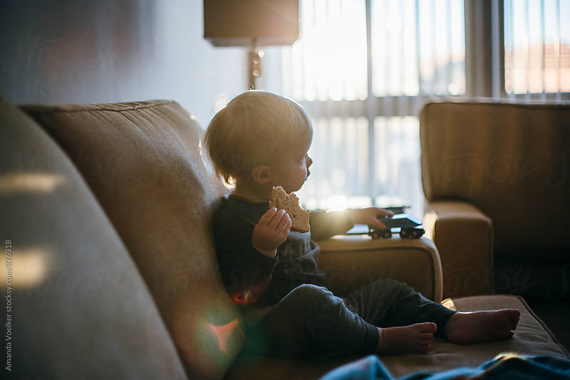 Profile of a Toddler boy Eating bread in the morning light by Amanda Voelker for Stocksy United