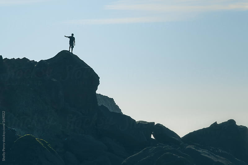 Man silhouetted with arm out atop large costal boulder by Shelly Perry for Stocksy United