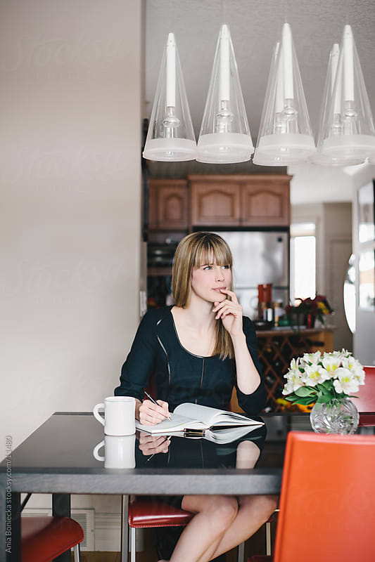 A beautiful woman thinking at the dining room table by Ania Boniecka for Stocksy United