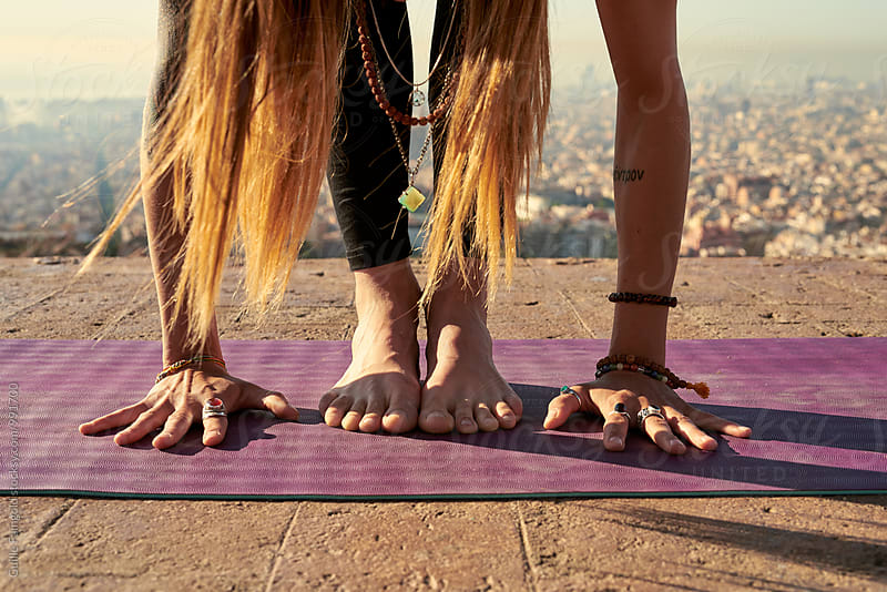 Close-up of barefoot woman preparing for pose on rug by Guille Faingold for Stocksy United