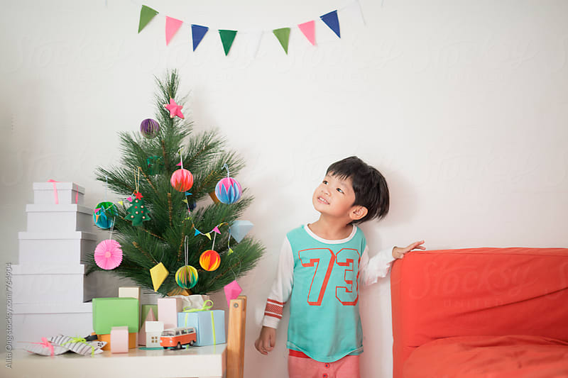 Happy kid looking at holiday tree by Alita Ong for Stocksy United