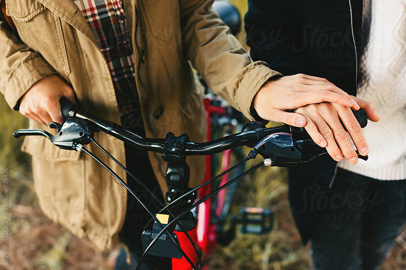 Hands of a couple on a bicycle handlebar. by BONNINSTUDIO for Stocksy United