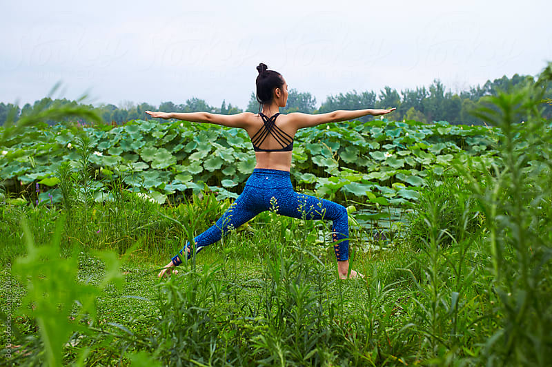 young asian woman playing Yoga by the lotus lake by cuiyan Liu for Stocksy United
