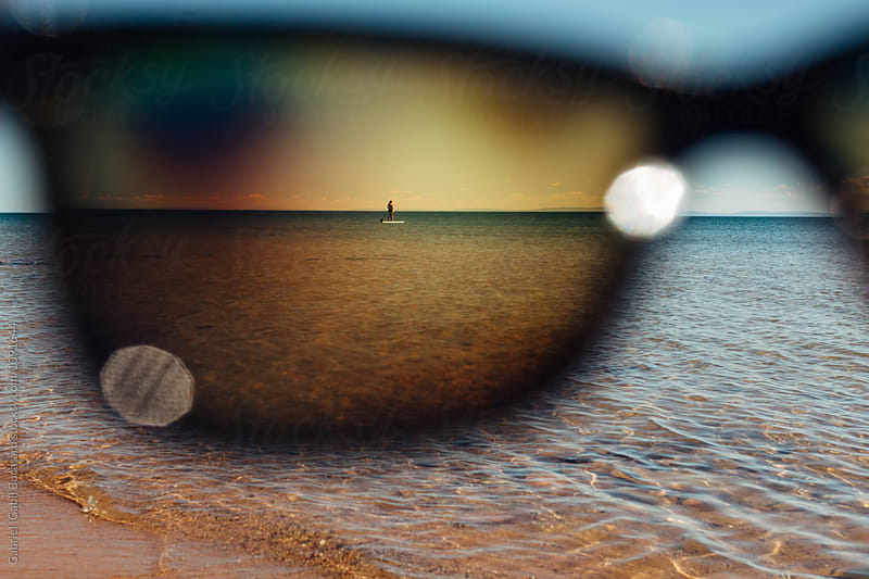 Mother and daughter on a paddleboard through a sunglass lens by Gabriel (Gabi) Bucataru for Stocksy United