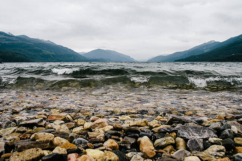 Low angle photo of waves coming toward a shoreline covered in pebbles by Justin Mullet for Stocksy United
