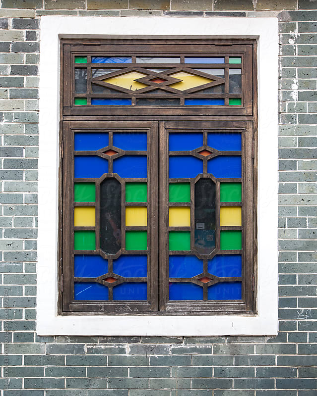 Old brightly colored and designed traditional house window in a Chinese village by Lawrence del Mundo for Stocksy United